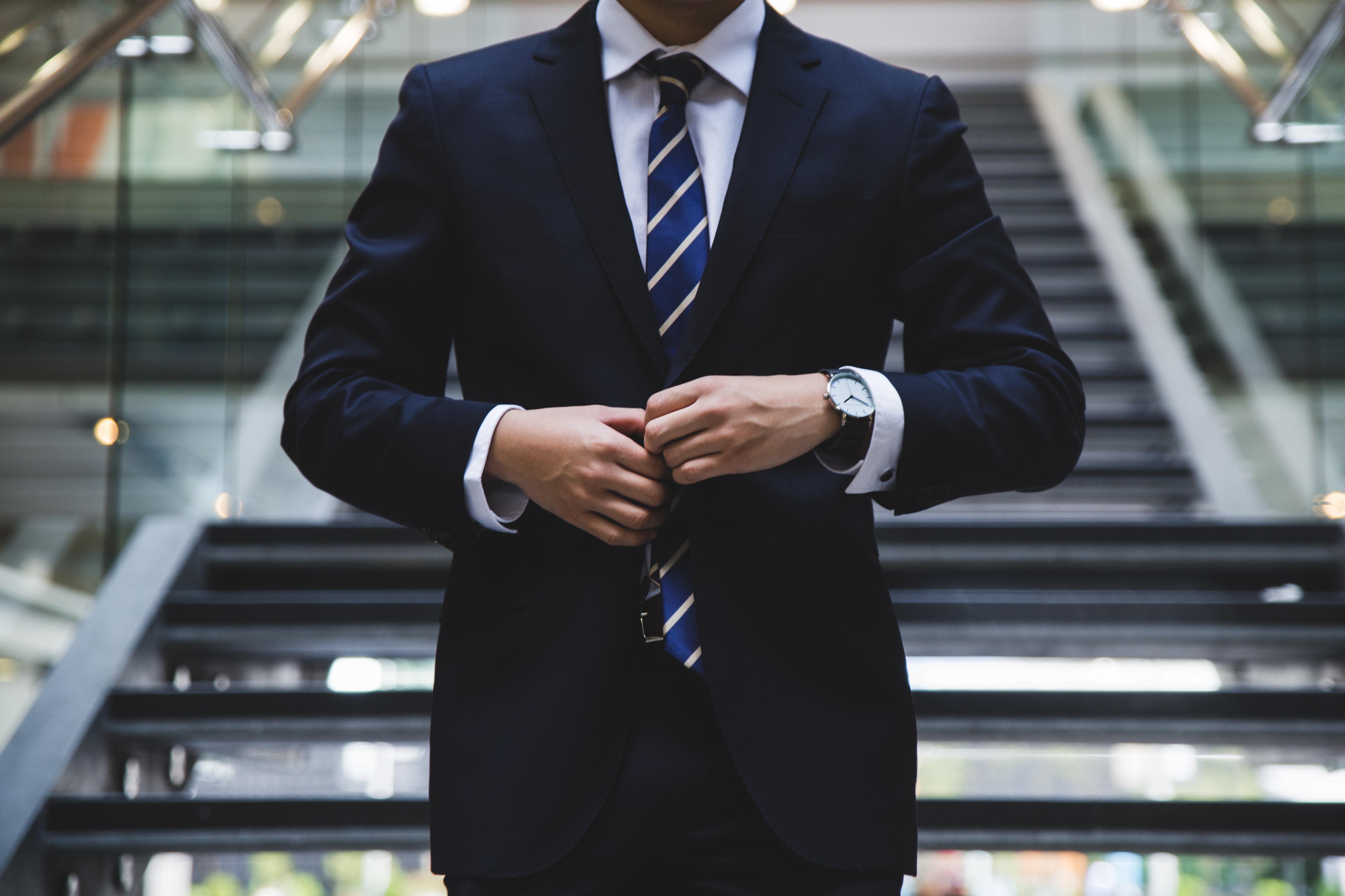 穿著藍色西裝的上班族男性在樓梯前扣夾克釦子