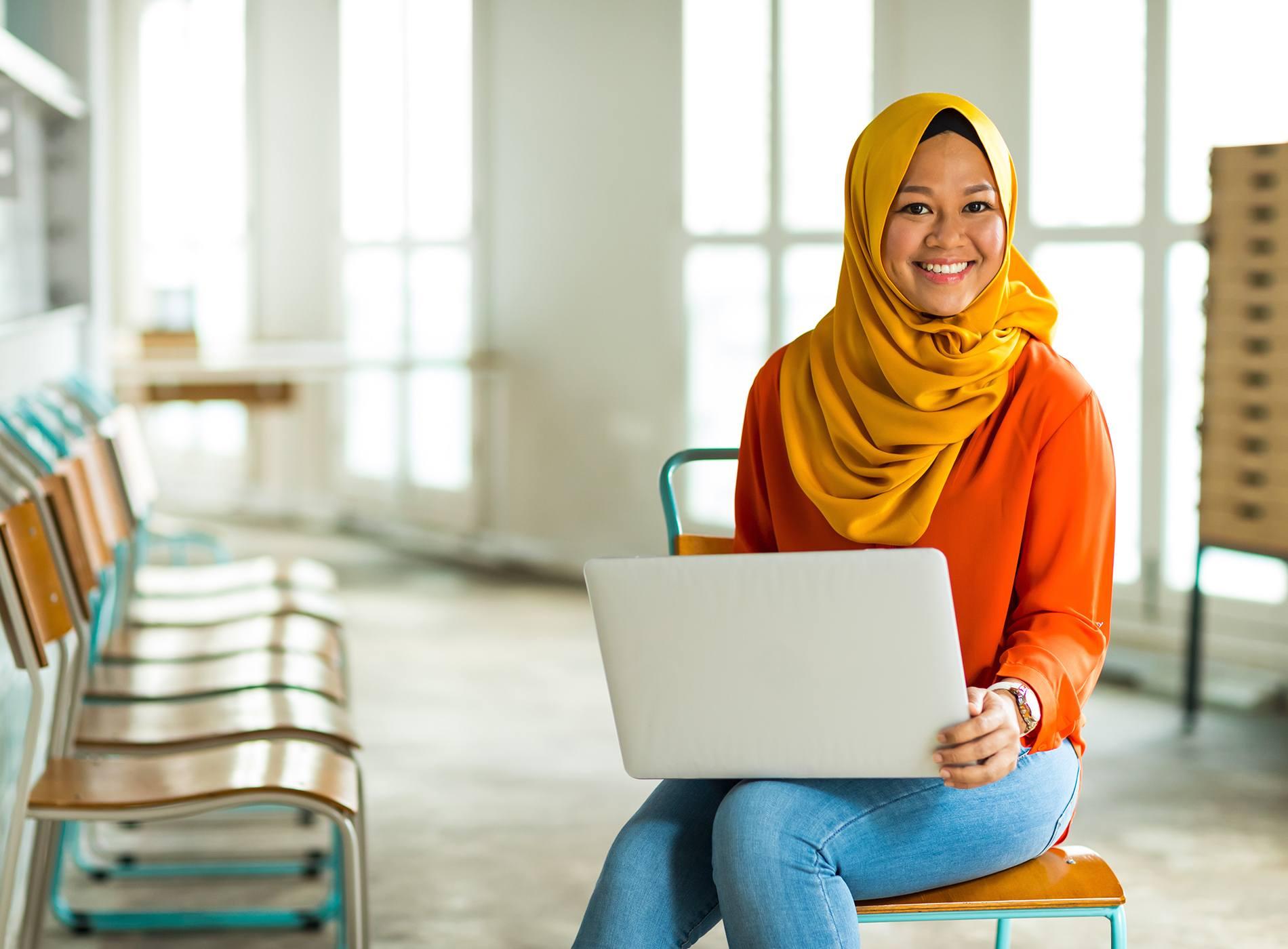 坐在椅子上使用筆記型電腦的女性
