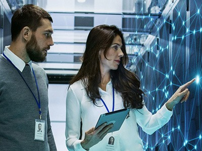 Man and woman standing in data center